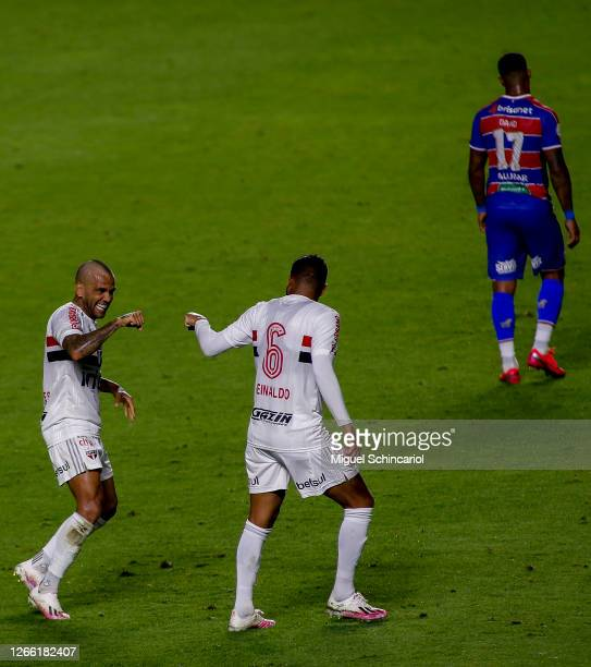 Dani Alves of Sao Paulo celebrates with teammate player Reinaldo after scoring his team first goal during a match between Sao Paulo and Fortaleza as...