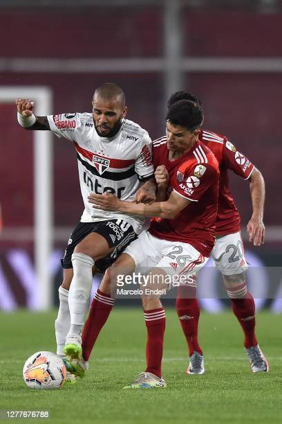 Dani Alves of Sao Paulo competes for the ball with Ignacio Fernández of River Plate during a Copa CONMEBOL Libertadores 2020 group D match between...