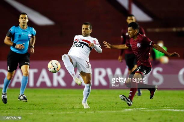 Dani Alves of Sao Paulo fights for the ball with Brian Aguirre of Lanus during a second round match of Copa CONMEBOL Sudamericana 2020 between Lanus...