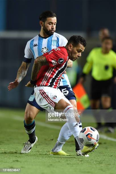 Dani Alves of Sao Paulo fights for the ball with Eugenio Mena of Racing Club during a match between Racing Club and Sao Paulo as part of Group E of...