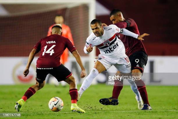 Dani Alves of Sao Paulo fights for the ball with José Sand and Lucas Vera Piris of Lanus during a second round match of Copa CONMEBOL Sudamericana...
