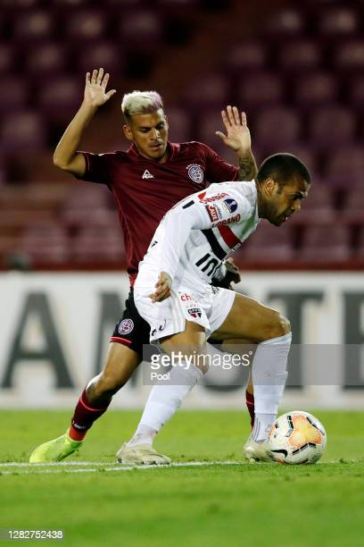 Dani Alves of Sao Paulo fights for the ball with Lucas Vera Piris of Lanus during a second round match of Copa CONMEBOL Sudamericana 2020 between...