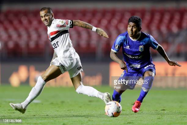 Dani Alves of Sao Paulo fights for the ball with Pablo Labrin of Binacional during a Group D Match of Copa CONMEBOL Libertadores 2020 between Sao...