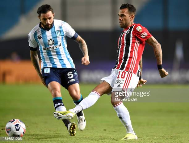 Dani Alves of Sao Paulo kicks the ball against Eugenio Mena of Racing Club during a match between Racing Club and Sao Paulo as part of Group E of...