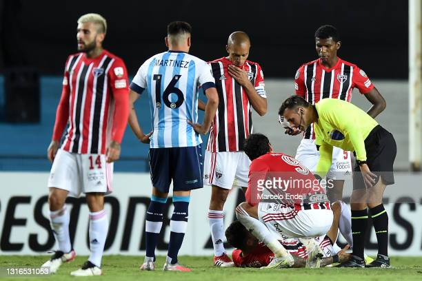 Dani Alves of Sao Paulo lies on the pitch after suffering an injury as he talks to Referee Piero Maza during a match between Racing Club and Sao...