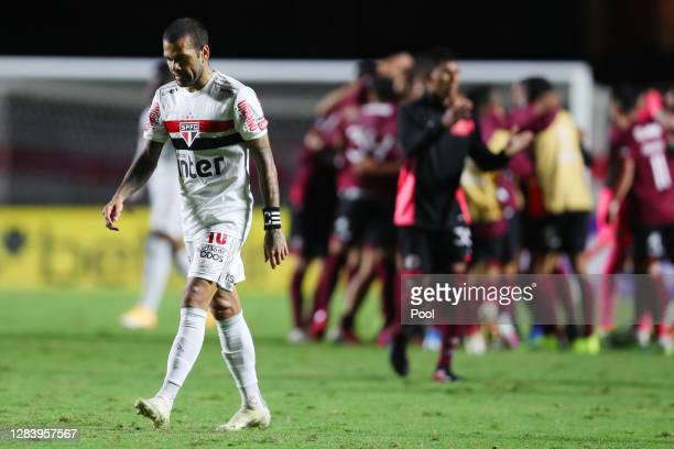 Dani Alves of Sao Paulo looks dejected as players Lanus celebrate qualifying to the next round after a second leg match of Copa CONMEBOL Sudamericana...