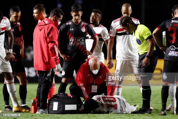Dani Alves of Sao Paulo receives medical attention during a match between Sao Paulo and Rentistas as part of Group E of Copa CONMEBOL Libertadores...