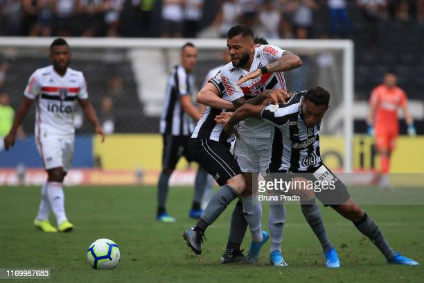 Dani Alves of Sao Paulo struggles for the ball with a Joao Paulo and Luiz Fernando of Botafogo during a match between Botafogo and Sao Paulo as part...