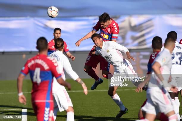 Dani Calvo of Elche CF scores his team's first goal under pressure from Raphael Varane of Real Madrid during the La Liga Santander match between Real...