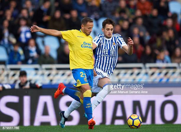 Dani Castellano of UD Las Palmas duels for the ball with Adnan Januzaj of Real Sociedad during the La Liga match between Real Sociedad de Futbol and...