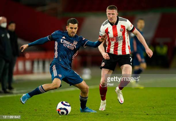 Dani Ceballos of Arsenal makes a pass whilst under pressure from John Lundstram of Sheffield United during the Premier League match between Sheffield...