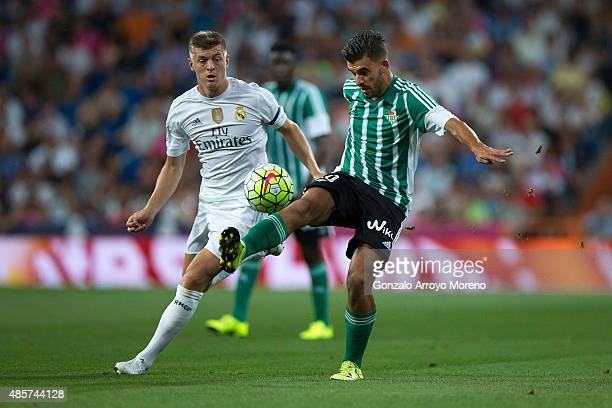 Dani Ceballos of Real Betis Balompie competes for the ball with Toni Kroos of Real Madrid CF during the La Liga match between Real Madrid CF and Real...