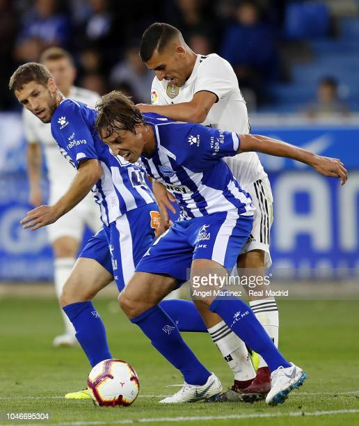 Dani Ceballos of Real Madrid competes for the ball with Tomas Pina of Deportivo Alaves during the La Liga match between Deportivo Alaves and Real...