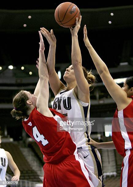 Dani Kubik of the Brigham Young University Cougars tries to get off a shot over Kim Smith of the Utah Utes during the championship of the Women's...
