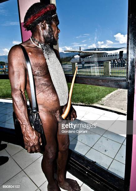 Dani man wearing kotekas (penis gourd-sheath) in the airport waiting the the departure of his flight, Baliem Valley, Western New Guinea, Indonesia.