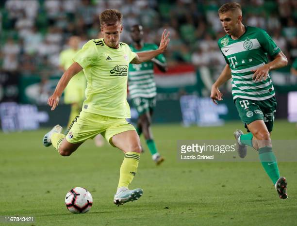 Dani Olmo of GNK Dinamo Zagreb shoots on goal next to Eldar Civic of Ferencvarosi TC during the UEFA Champions League Third Qualifying Round match...
