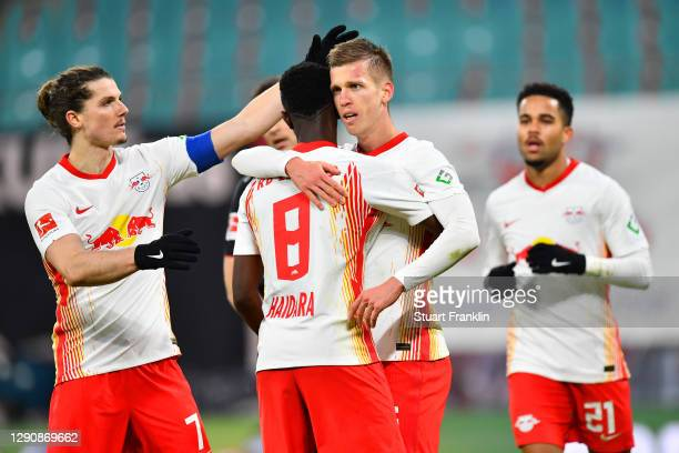 Dani Olmo of RB Leipzig celebrates with Amadou Haidara and Marcel Sabitzer after scoring their team's second goal during the Bundesliga match between...