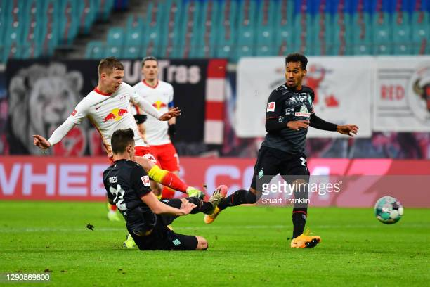 Dani Olmo of RB Leipzig scores their team's second goal under pressure from Marco Friedl of Werder Bremen during the Bundesliga match between RB...