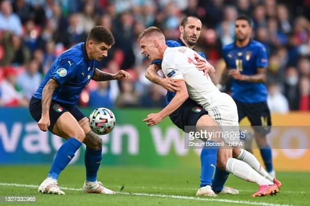 Dani Olmo of Spain is challenged by Giorgio Chiellini of Italy as Giovanni Di Lorenzo of Italy looks to gain possession during the UEFA Euro 2020...