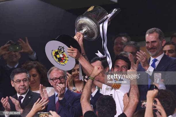 Dani Parejo of Valencia CF celebrates with the trophy next to King Felipe VI of Spain at the end of the Spanish Copa del Rey match between Barcelona...