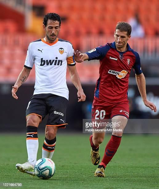 Dani Parejo of Valencia competes for the ball with Darko Brasanac of Osasuna during the Liga match between Valencia CF and CA Osasuna at Estadio...