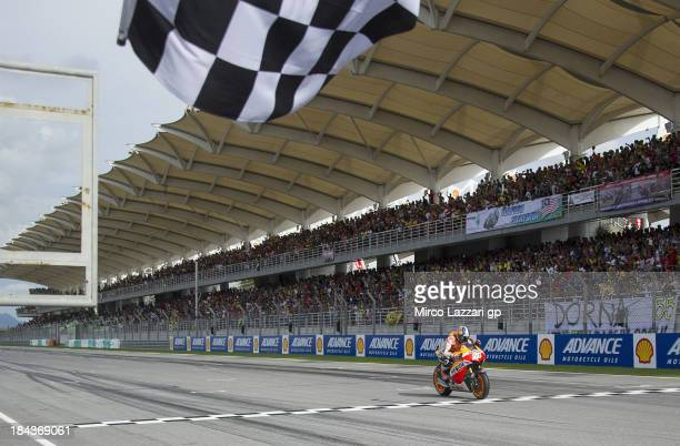 Dani Pedrosa of Spain and Repsol Honda Team crosses the finish line to win the MotoGP Of Malaysia Race at Sepang Circuit on October 13 2013 in Kuala...