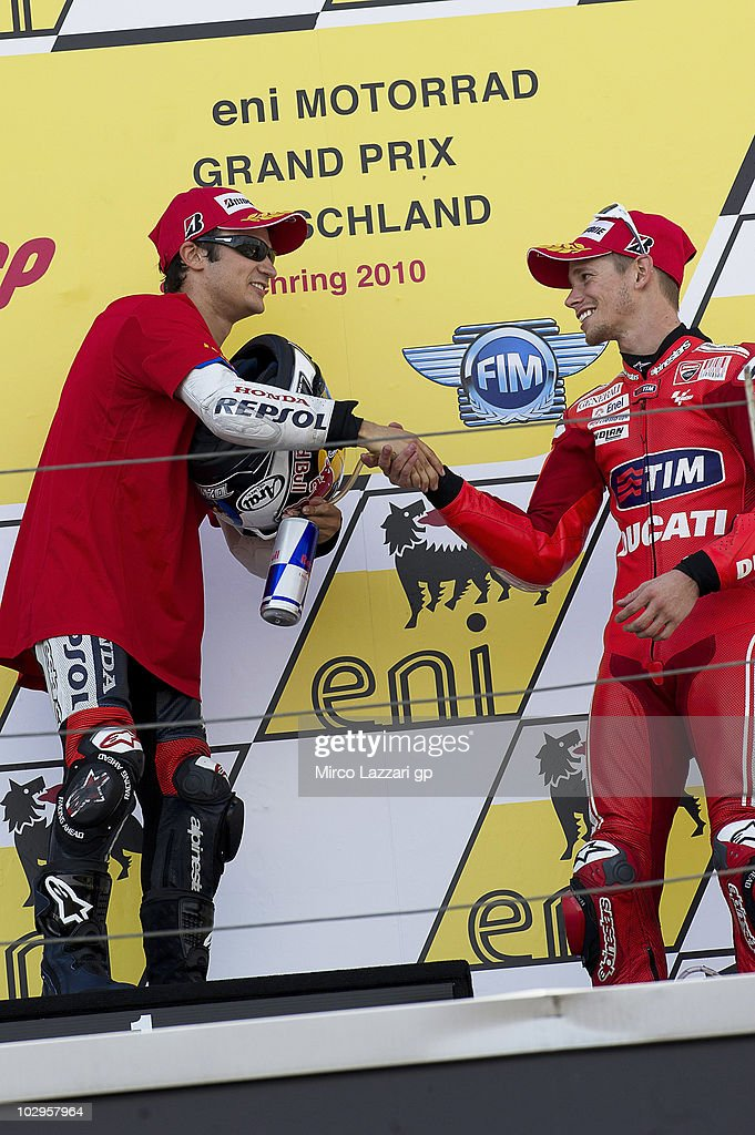 Dani Pedrosa of Spain and Repsol Honda Team greets Casey Stoner of Australia and Ducati Marlboro Team on the podium at the end of the MotoGP race of Grand Prix of Germany at Sachsenring Circuit on July 18, 2010 in Hohenstein-Ernstthal, Germany.