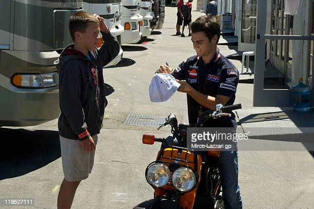 Dani Pedrosa of Spain and Repsol Honda Team signs autograph for fan in paddock during the Red Bull U.S. Grand Prix at Mazda Raceway Laguna Seca on...