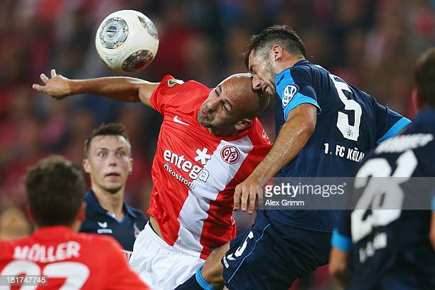 Dani Schahin of Mainz jumps for a header with Dominic Maroh of Koeln during the DFB Cup second round match between 1 FSV Mainz 05 and 1 FC Koeln at...
