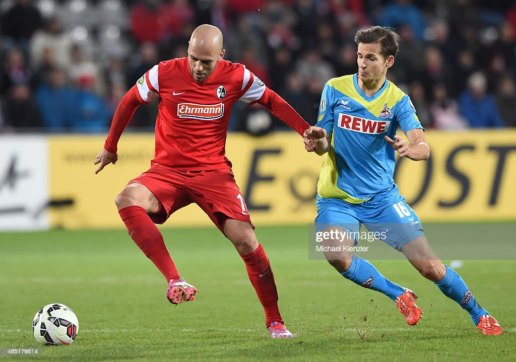 Dani Schahin (L) of SC Freiburg challenges Pawel Olkowski (R) of 1. FC Koeln during the DFB Cup between SC Freiburg and 1. FC Koeln at Schwarzwald-Stadium on March 3, 2015 in Freiburg, Germany.