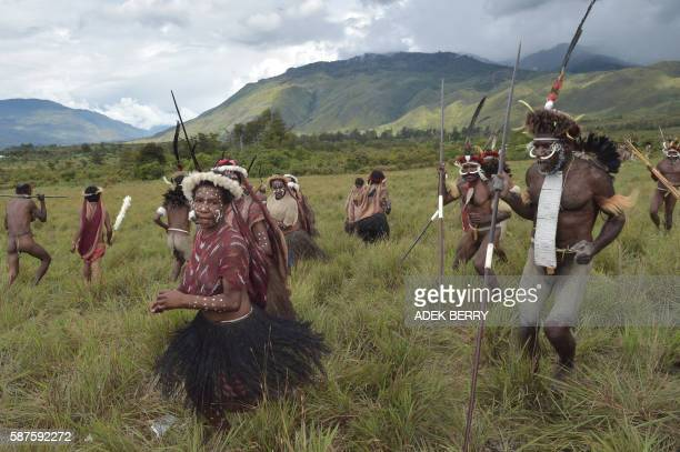 Dani tribespeople perform a mock tribal war battle during the 27th annual Baliem Valley Festival in Walesi district in Wamena, Papua Province on...