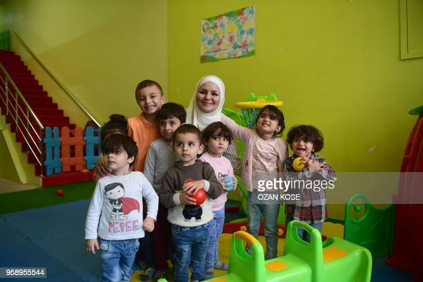 Dania Abdulbaqi creche owner poses with children during an interview with AFP in Gaziantep in the southwest province of Turkey on May 2 2018 In the...