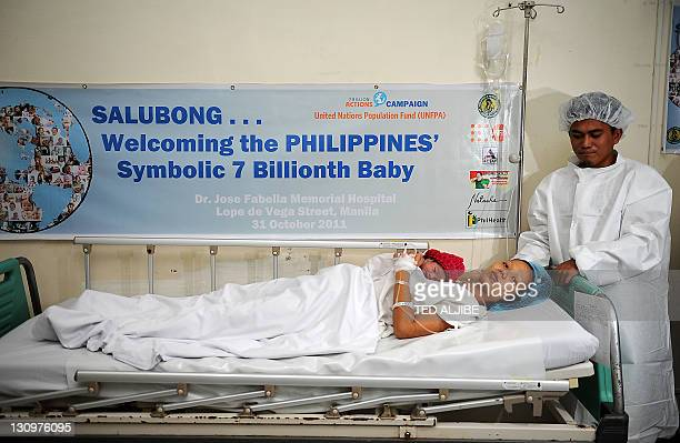Danica Mae Camacho the Philippine's symbolic 7 billionth baby is coddled by her mother Camille during a welcoming ceremony after she was given birth...
