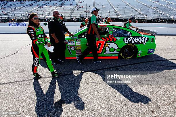 Danica Patrick, driver of the GoDaddy Chevrolet, left, walks with her car as it is pushed down the grid prior to qualifying for the NASCAR Sprint Cup...