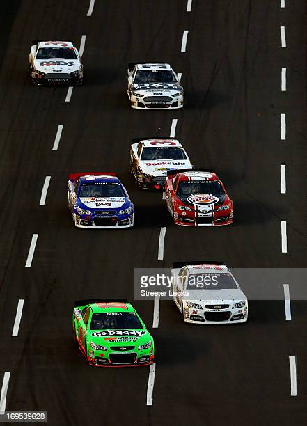 Danica Patrick driver of the GoDaddycom Chevrolet and JJ Yeley driver of the World Trade Barter Solutions Chevrolet lead a group of cars during the...