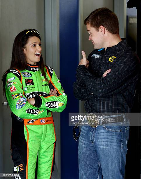 Danica Patrick driver of the GoDaddycom Chevrolet talks with Cup Series Ricky Stenhouse Jr driver of the Best Buy Ford in the garage during practice...
