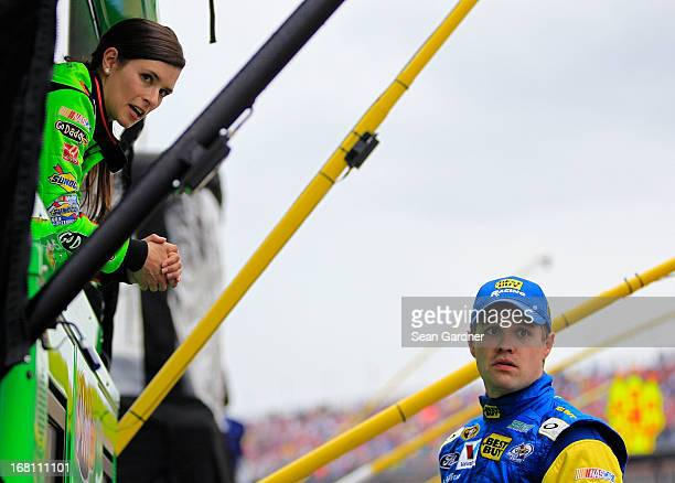 Danica Patrick driver of the GoDaddycom Chevrolet talks with Ricky Stenhouse Jr driver of the Best Buy Ford as the race was under caution due to rain...