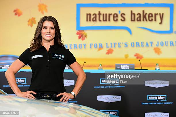 Danica Patrick driver of the StewartHaas Racing Chevrolet poses for a photo opportunity after she announced a multiyear deal partnership with...