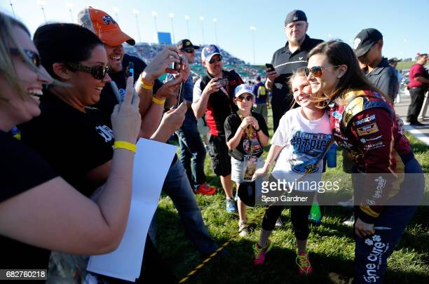 Danica Patrick driver of the Wonder Woman/One Cure Ford poses for a photo with a fan before the Monster Energy NASCAR Cup Series Go Bowling 400 at...