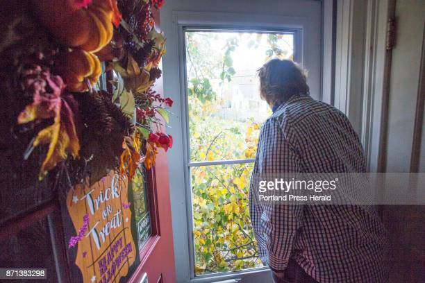 Danice Jacobson looks out of a window of her Westminster Ave house which is buried in a large tree that came down in a storm on Sunday night Jacobson...