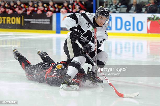 Danick Martel of the BlainvilleBoisbriand Armada skates with the puck in front of a falling Matthieu Desautels of the Baie Comeau Drakkar during the...