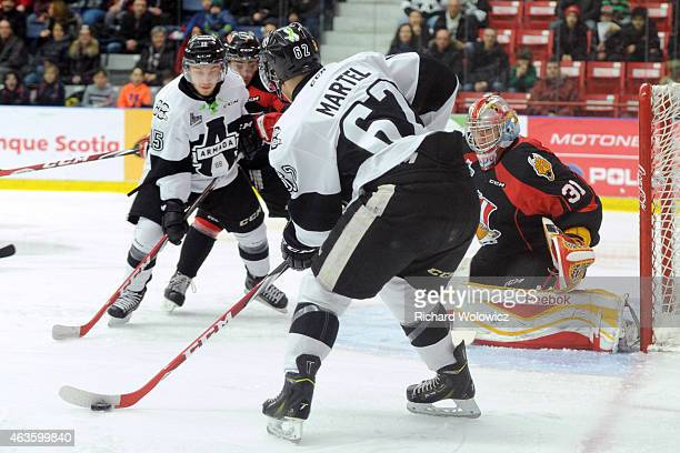 Danick Martel of the BlainvilleBoisbriand Armada stick handles the puck in front of Philippe Cadorette of the Baie Comeau Drakkar during the QMJHL...