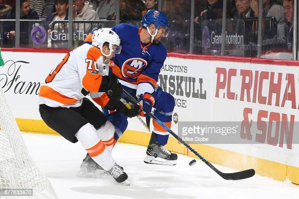 Danick Martel of the Philadelphia Flyers battles for the puck along the boards against Dennis Seidenberg of the New York Islanders in his first NHL...