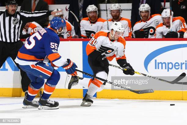Danick Martel of the Philadelphia Flyers battles for the puck along the boards against Johnny Boychuk of the New York Islanders in his first NHL game...