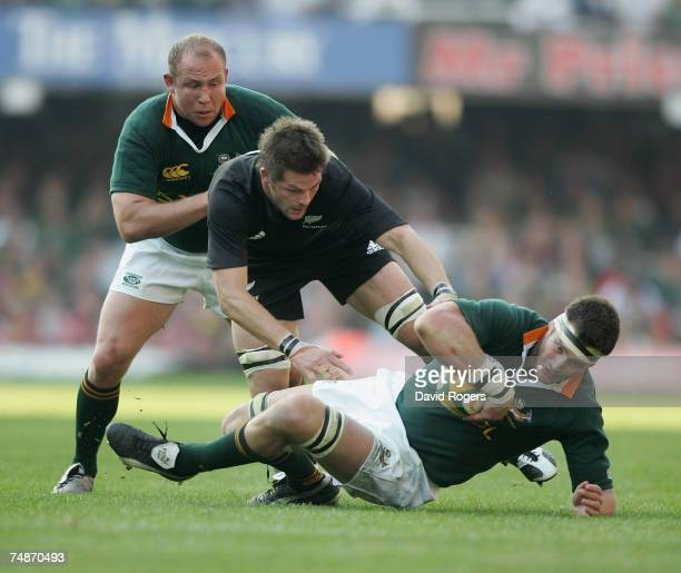 Danie Rossouw of South Africa is tackled by Richie McCaw watched by Gary Botha during the 2007 TriNations match between South Africa and New Zealand...