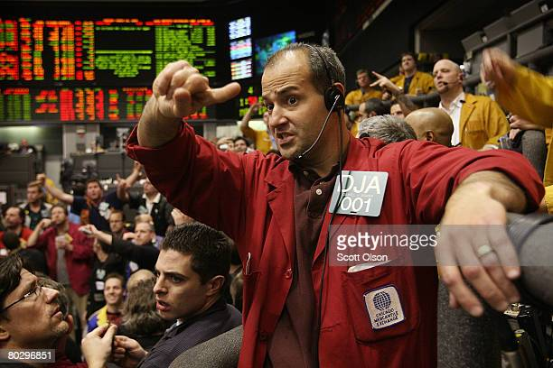 Daniel Adams signals offers in the Eurodollar futures pit at the Chicago Mercantile Exchange following the announcement from the Federal Open Market...