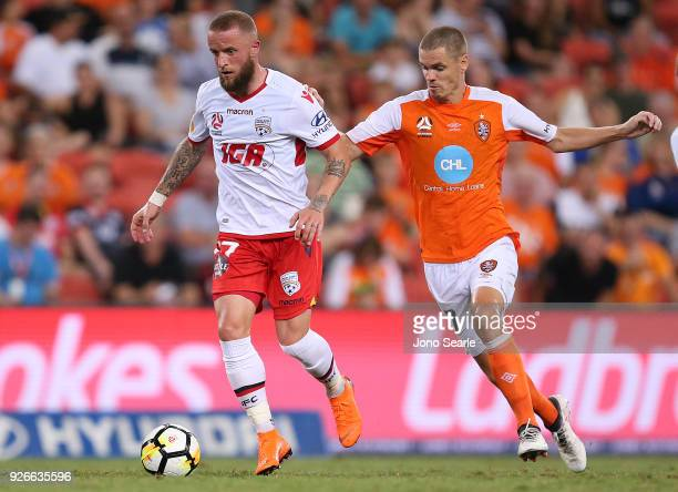Daniel Adlung of Adelaide United gets past Thomas Kristensen of the Brisbane Roar during the round 22 ALeague match between the Brisbane Roar and...