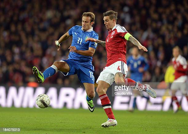 Daniel Agger of Denmark and Alberto Gilardinoi of Italy compete for the ball during the FIFA 2014 World Cup Qualifying group B match between Denmark...