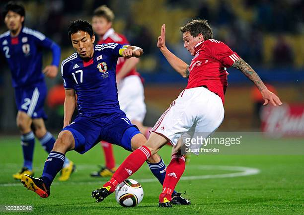 Daniel Agger of Denmark takes on Makoto Hasebe of Japan during the 2010 FIFA World Cup South Africa Group E match between Denmark and Japan at the...