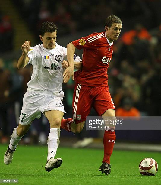 Daniel Agger of Liverpool holds off a challenge from Marius Loan Bilasco of Unirea Urziceni during the UEFA Europa League Round 32 first leg match...